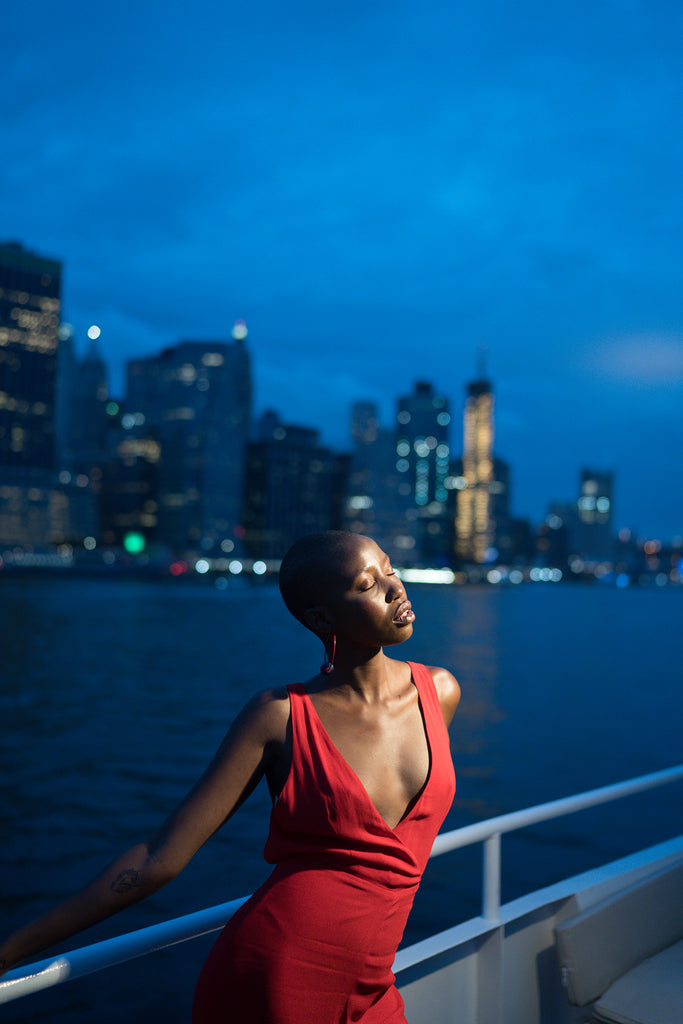 Sara France photograph of woman on boat wearing red dress cityscape in background