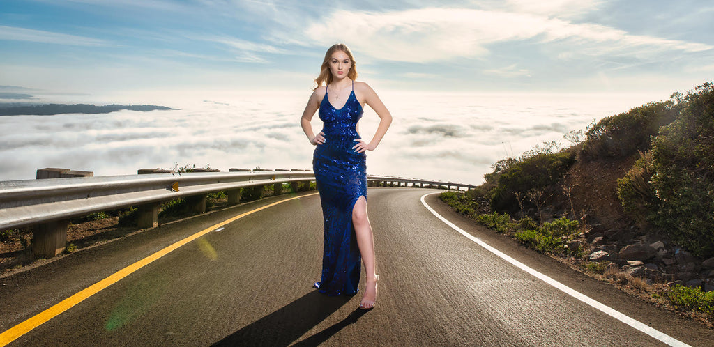 Steve Batz portrait of woman on road blacktop in blue dress high heels blue sky