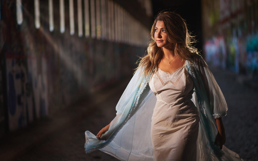 Steve Batz woman in white dress in old abandoned railway tunnel light streaking