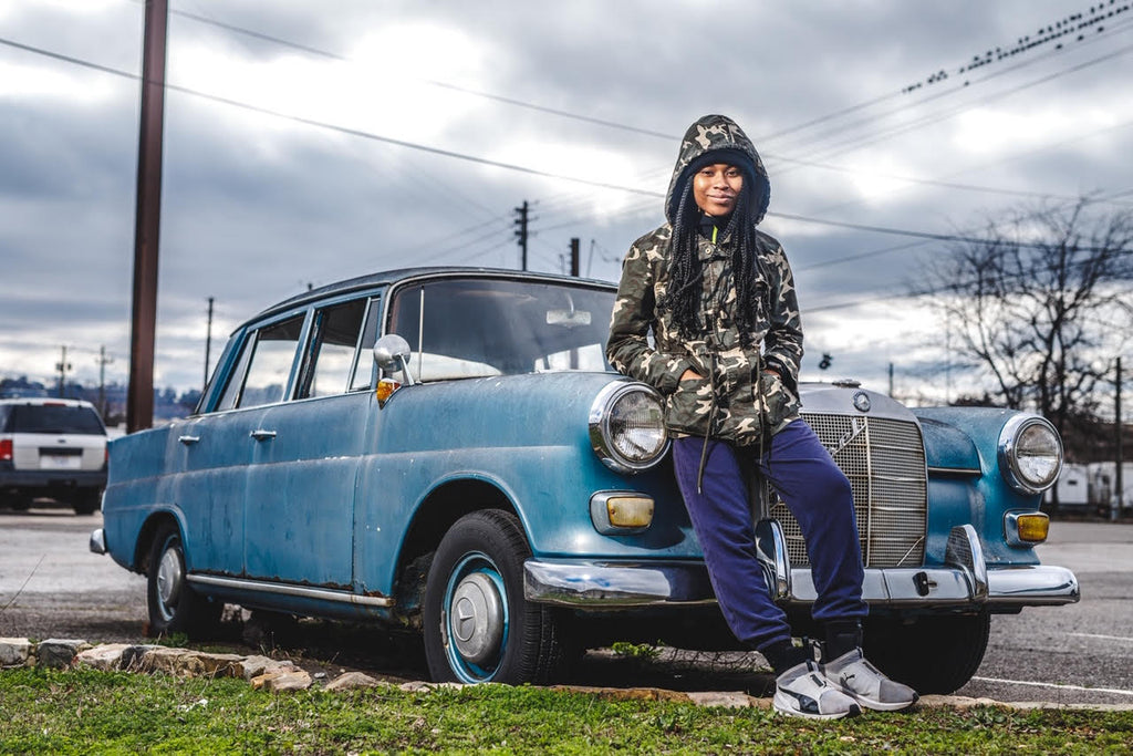 Tosha Gaines young woman in hoody leaning on vintage Mercedes Benz sedan outside birds on powerlines winter