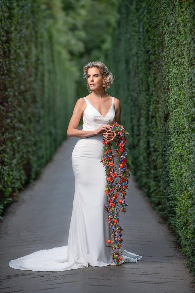 Yuliya Panchenko bride with bouquet standing in green hedgerow