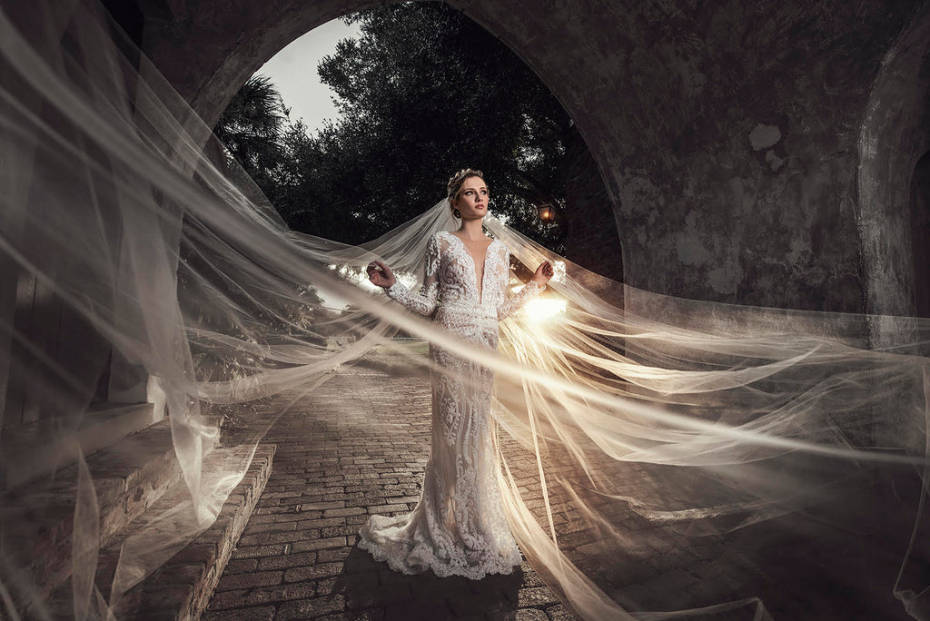 Yuliya Panchenko bride with large veil with sunlight in archway tunnel