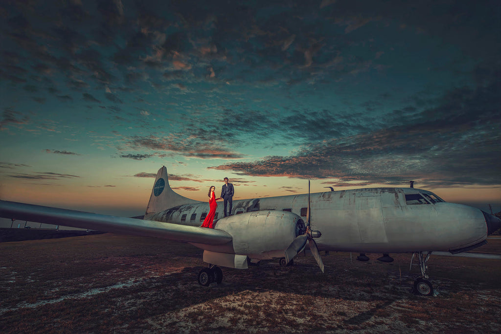 Yuliya Panchenko man and woman standing on wing and propeller of old aircraft wreck