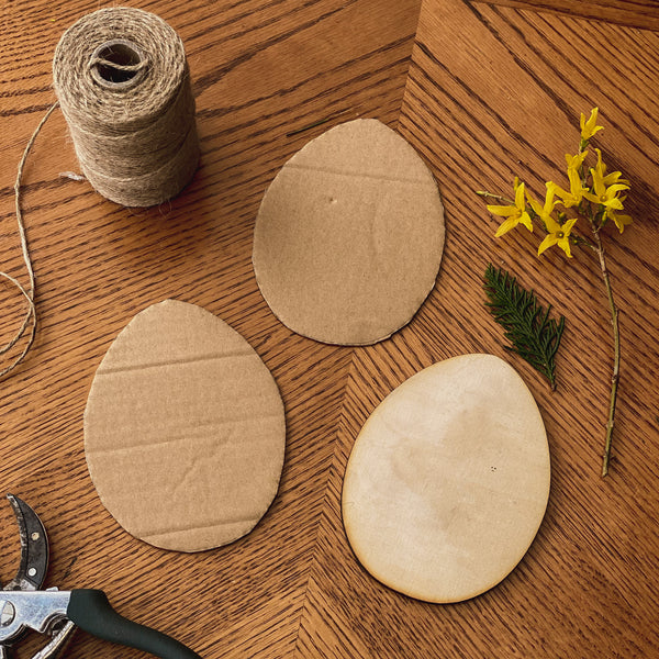 Draw an egg shape on cardboard and cut it out to create the base of your weaving board