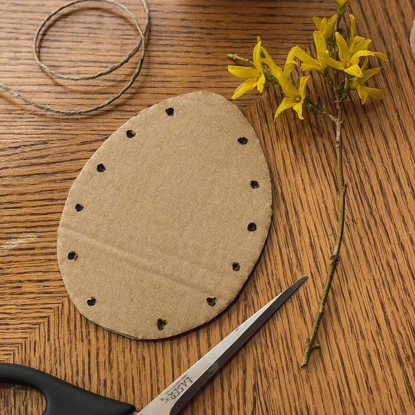 make dots on either side of the egg and the poke a hole through them. These will be the holes to thread your twine through