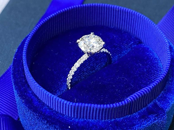 lab created diamond engagement ring with pave stones in blue box