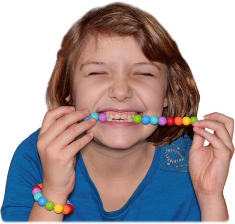 Girl chewing Munchables necklace and wearing bracelet