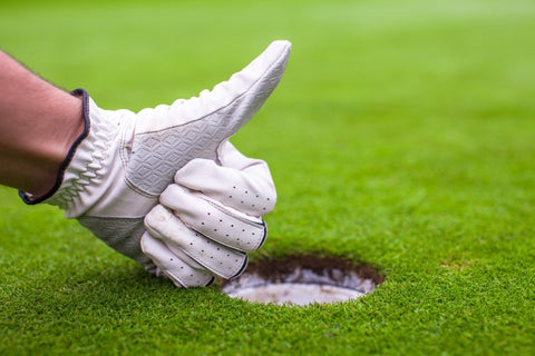 Man with golf glove giving thumbs up
