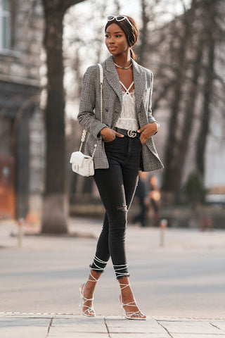 woman walking with a blazer over a bra outfit outside