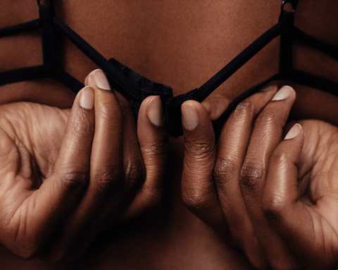 close up of womans hands fastening bra behind back