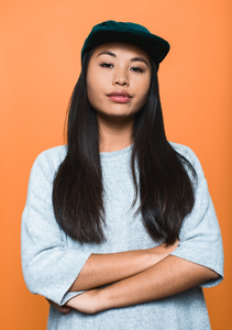 Asian lady wearing a grey top and cap in front of a orange background