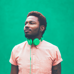 Man with green headphones standing against a green background