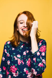 image of a lady wearing a floral top in front of a yellow background
