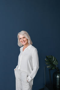 Older lady wearing a white top in-front of a dark blue background