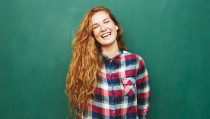 lady laughing wearing a chequered shirt in front of a green background