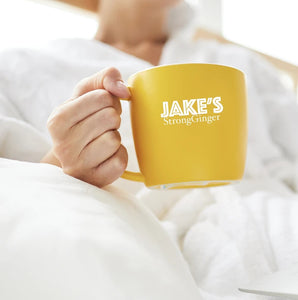 Person in robe drinking from a Jake's StrongGinger stamped mug.