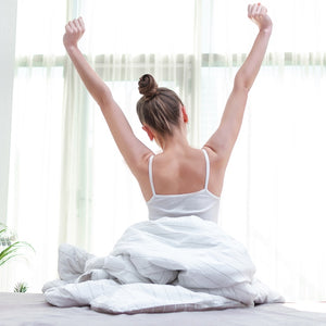 Woman stretching in bed after waking up in the morning.