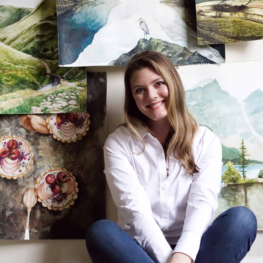 Courtney Hopkins smiling in front of her artwork