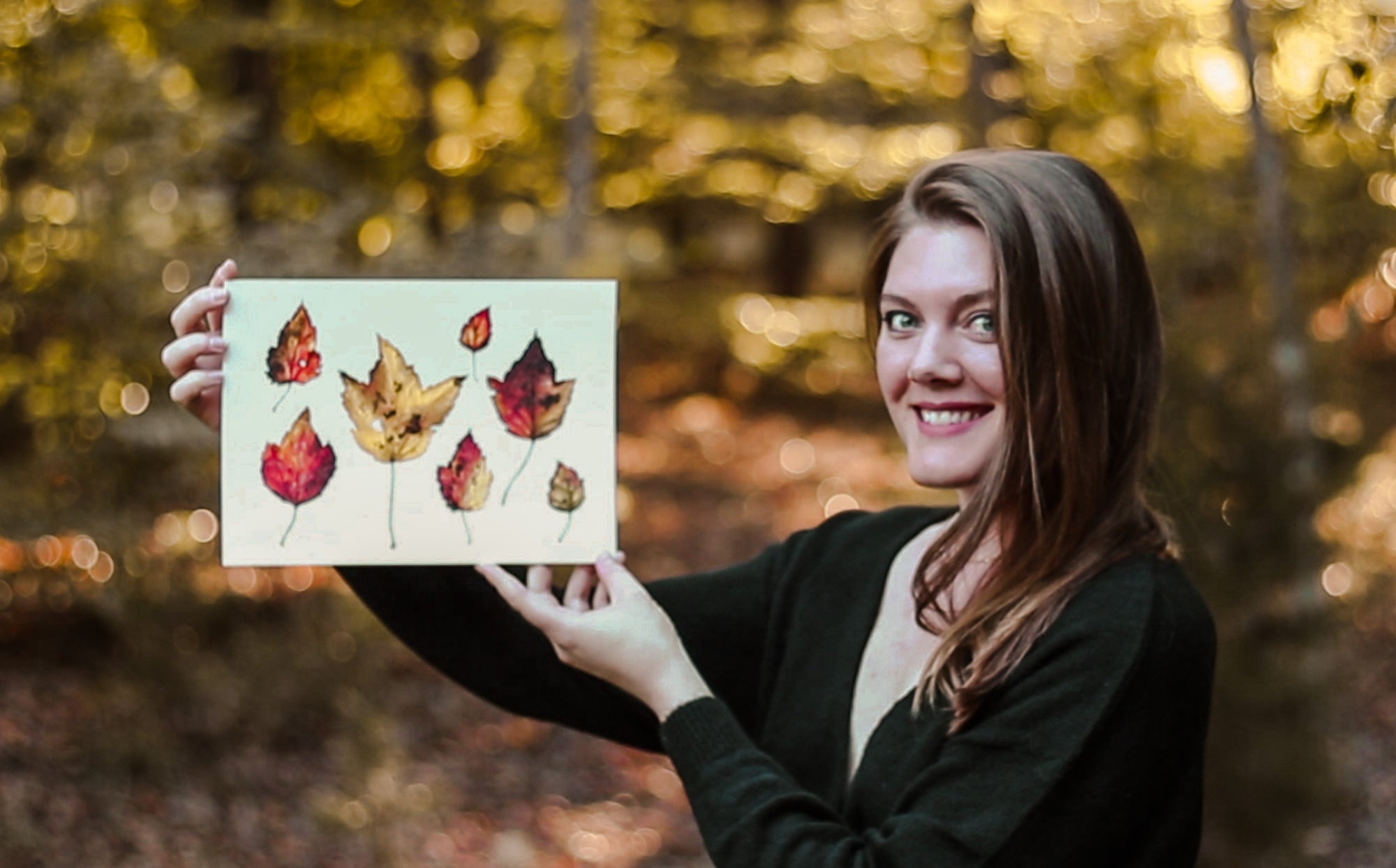 Courtney Hopkins holding up a painting of fall leaves