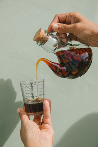 Herbal extract pouring into measuring glass
