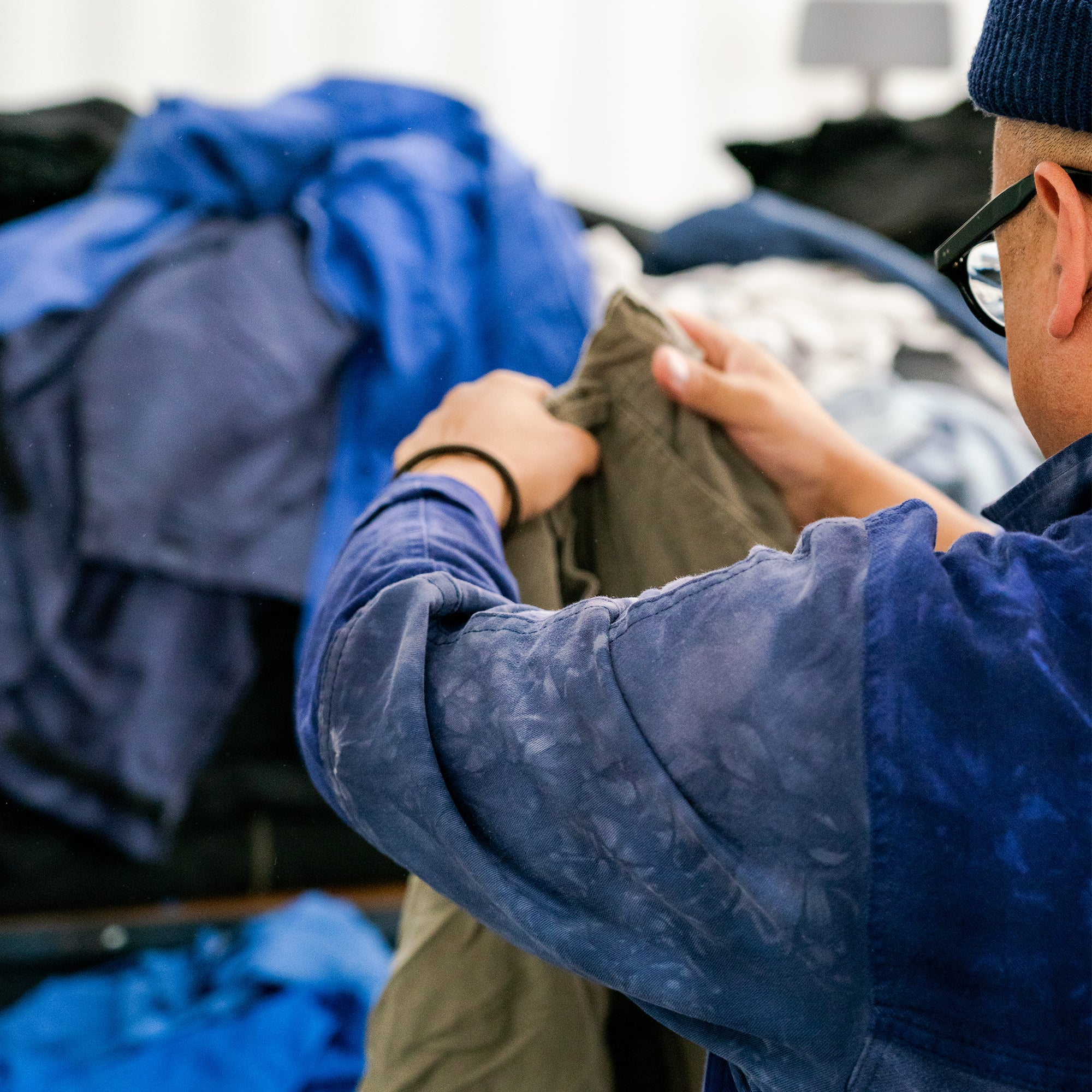 Image of man sorting a pile of reclamed fabric