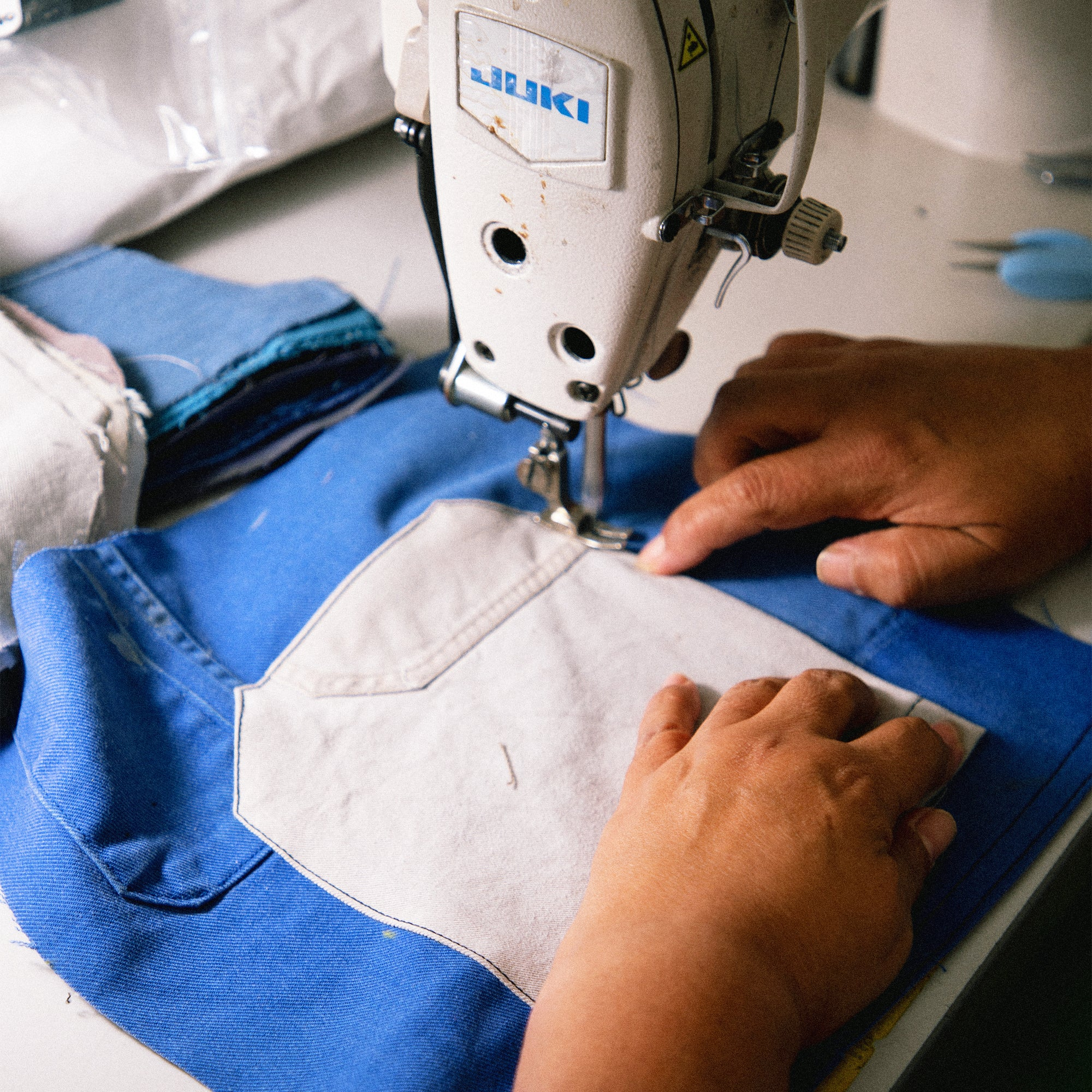 Image of person sewing pieces of Recraft garment together