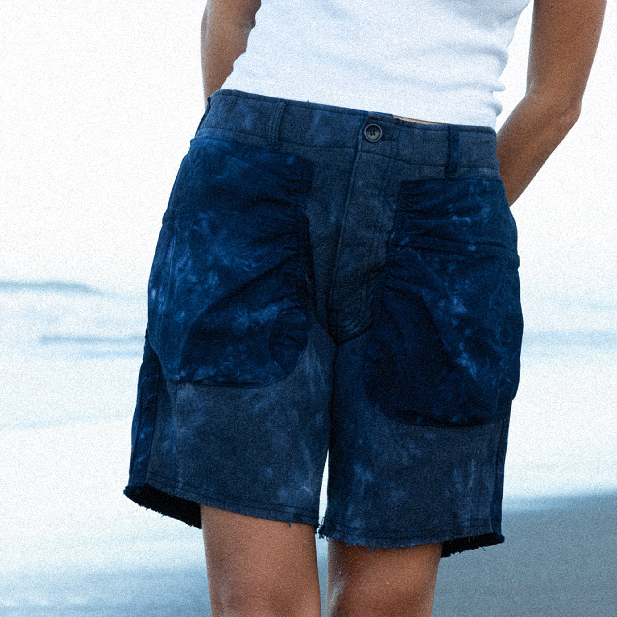 Closely cropped image of person wearing Recraft shorts in front of the ocean.