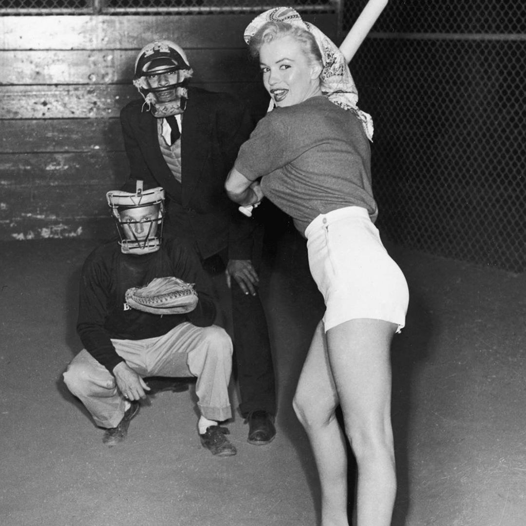 Marilyn Monroe posing at home plate with a baseball bat in high wasted shorts.