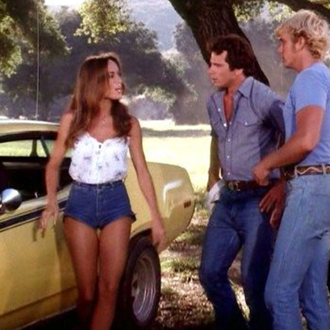 A still from the show Dukes of Hazard, showing Daisy Duke wearing her namesake cut-off shorts