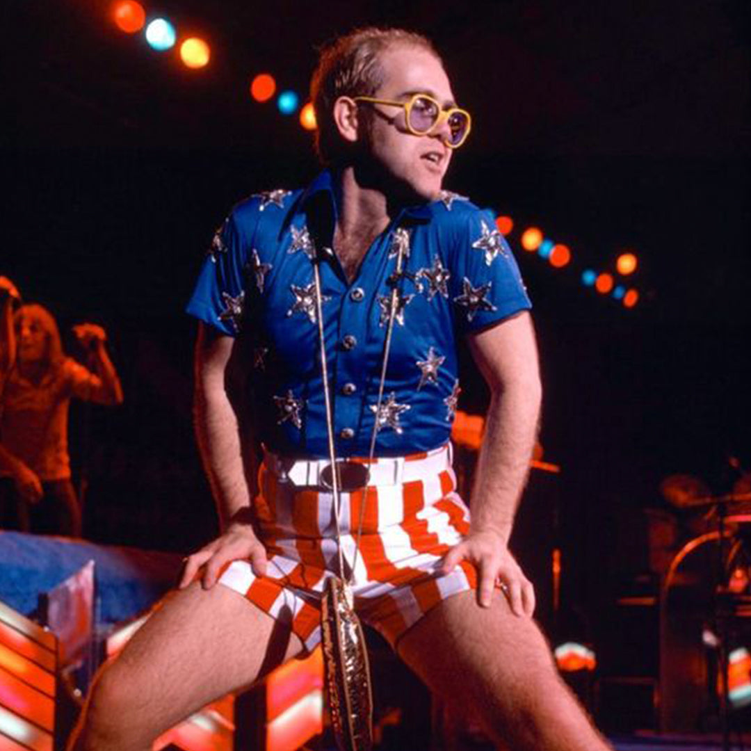 Elton John wearing red and white striped short shorts with a blue top emblazoned gold stars on stage at a performance.