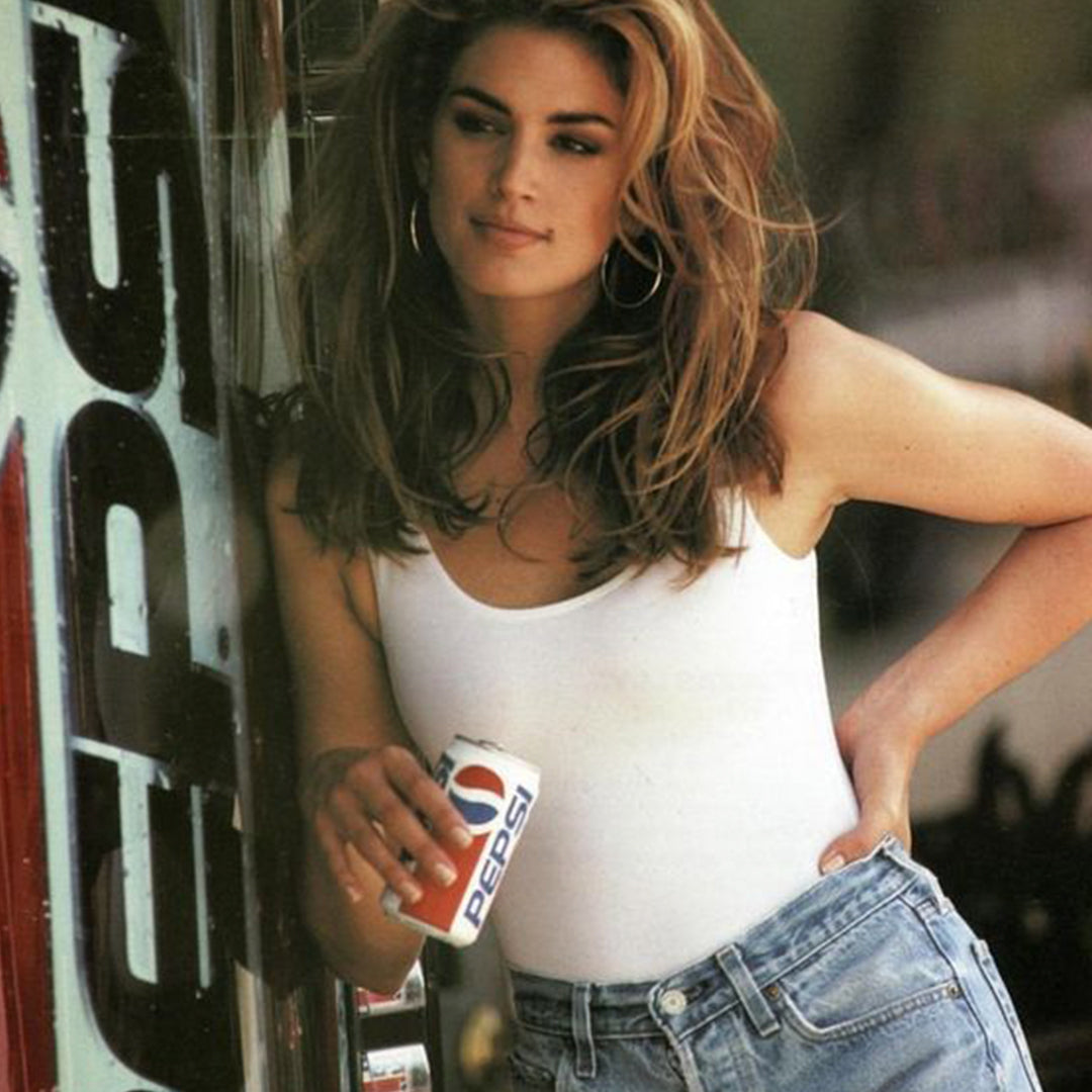 Cindy Crawford wearing jean shorts and white tank top in a still from a 90's Pepsi commercial.