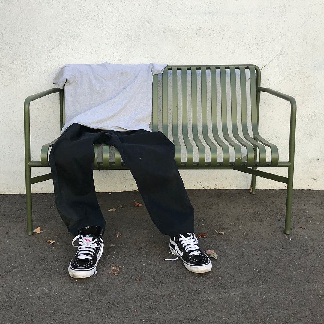 A tee-shirt, pants, and shoes placed on a bench to look like a person sitting