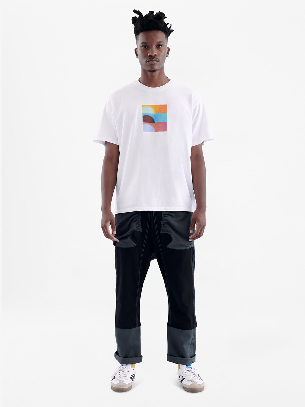 Model wearing white short sleeve cotton t-shirt with square multicolor abstract sunset graphic on chest