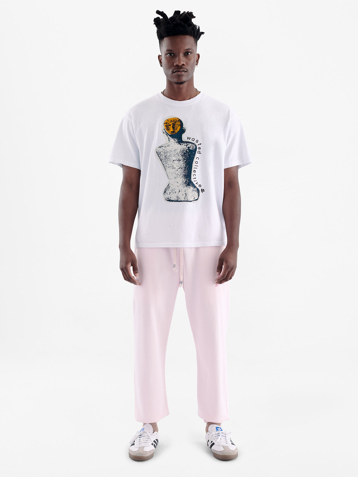 Male model wearing white recycled cotton t-shirt with collage graphic of ancient stone statue with yellow head