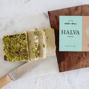 Slices of Seed + Mill Pistachio Halva, featuring branded packaging from our 8oz packages.
