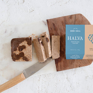 Slices of Seed + Mill Sea Salt Dark Chocolate halva, featuring branded packaging from our 8oz packages.