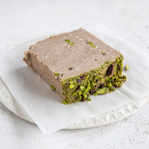 A plated slice of Seed + Mill Chocolate Pistachio Halva. Gluten-free, dairy-free, and vegan. Crumble into granola, cookies, yogurt, or melt on toast!
