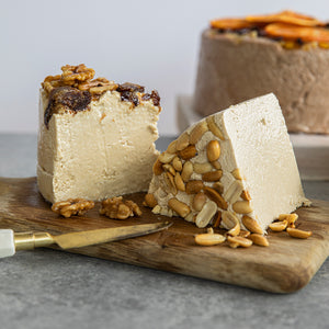Two lovely and enticing Seed + Mill favorites: Date Walnut and Crunchy Peanut Butter. Plated beautifully on a wooden cutting-board with a 6.6 lb round of Chocolate Orange in the background. All halva is gluten-free, dairy-free, and vegan.