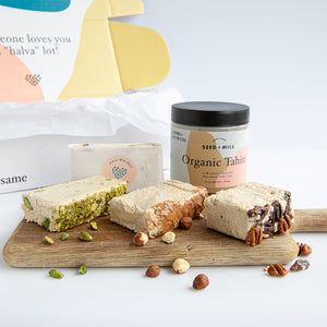 Sweet gifts from Seed + Mill. An assortment of Pistachio, Date Walnut, and Nougat halva; Our 'Nuts About Halva Pack.' Plated on a wood cutting board with a jar of Seed + Mill Tahini. Always gluten-free, dairy-free, and vegan. See our 'Create a Gift' page to put together something special for that special someone!