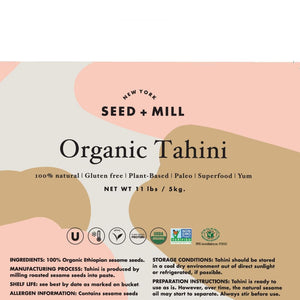 Seed + Mill Organic Tahini, 5K bucket. Closeup of label. Ingredients: 100% Organic Ethiopian sesame seeds. Storage: keep cool, dry, and out of direct sunlight. Stir before use.