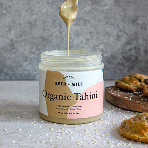 Seed + Mill Organic Tahini drizzled from a spoon. Next to chocolate chunk cookies. Gluten-free, dairy-free, and vegan. Check out our recipes page for inspiration.