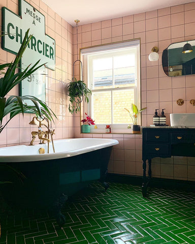Stylish pink and green bathroom with roll top bath