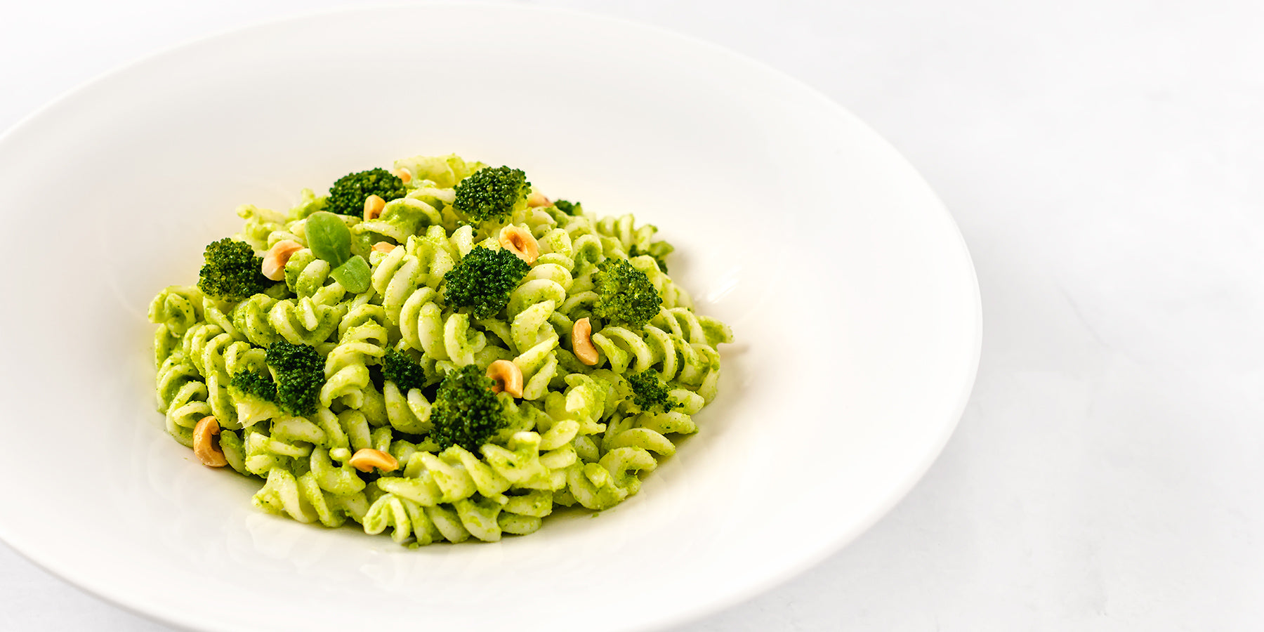 Plate of White Corn Fusilli with Broccoli Pesto and Hazelnuts