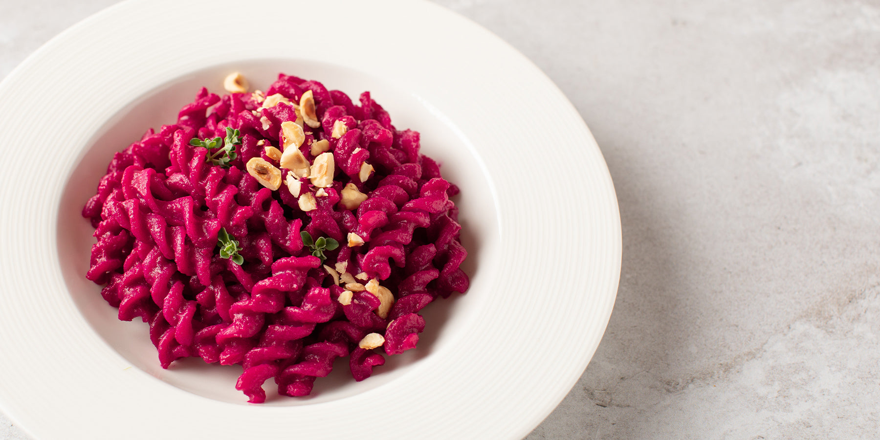 Plate of White Corn Fusilli with Beetroot and Hazelnuts