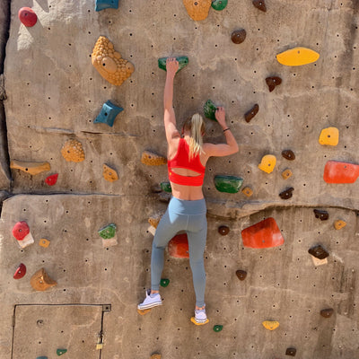 Girl climbing while wearing NEW Hula Crop Bra in Candy Apple (Red)
