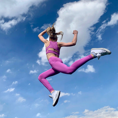 Girl jumping while wearing NEW Hula Crop Bra in Purple Clementine (Purple Pink)