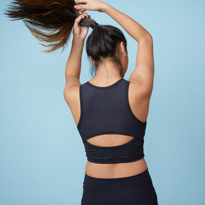 Girl doing hair while wearing NEW Hula Crop Bra in Starry Night (Black)