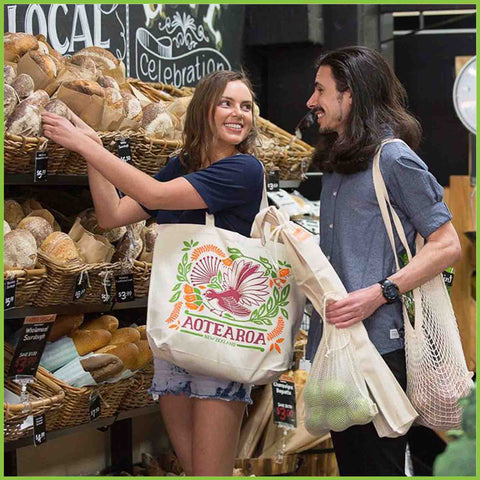 A happy couple shopping in a bakery, using their own reusable bags.
