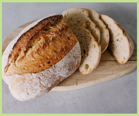 Fresh home baked bread sliced on a wooden chopping board.
