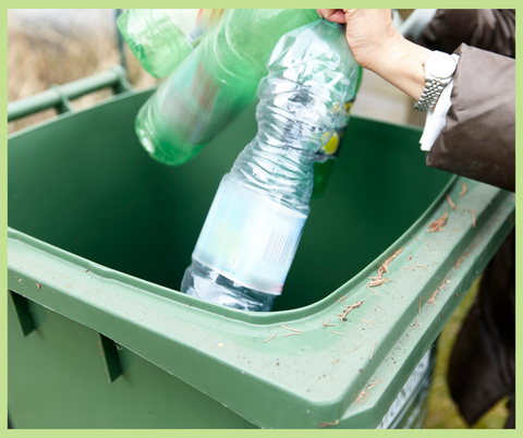 Two plastic bottles being put into a green recycling bin.